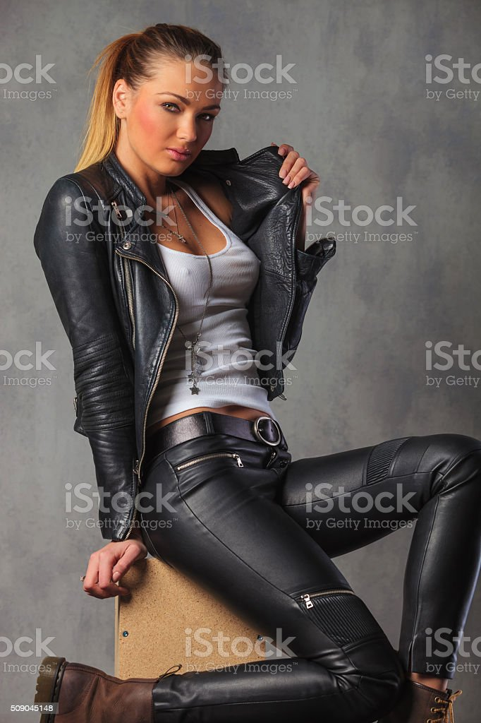 rocker girl in leather posing seated on box stock photo