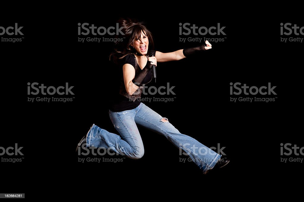 Rocker Girl Jumping and Singing into Microphone on Black Background royalty-free stock photo