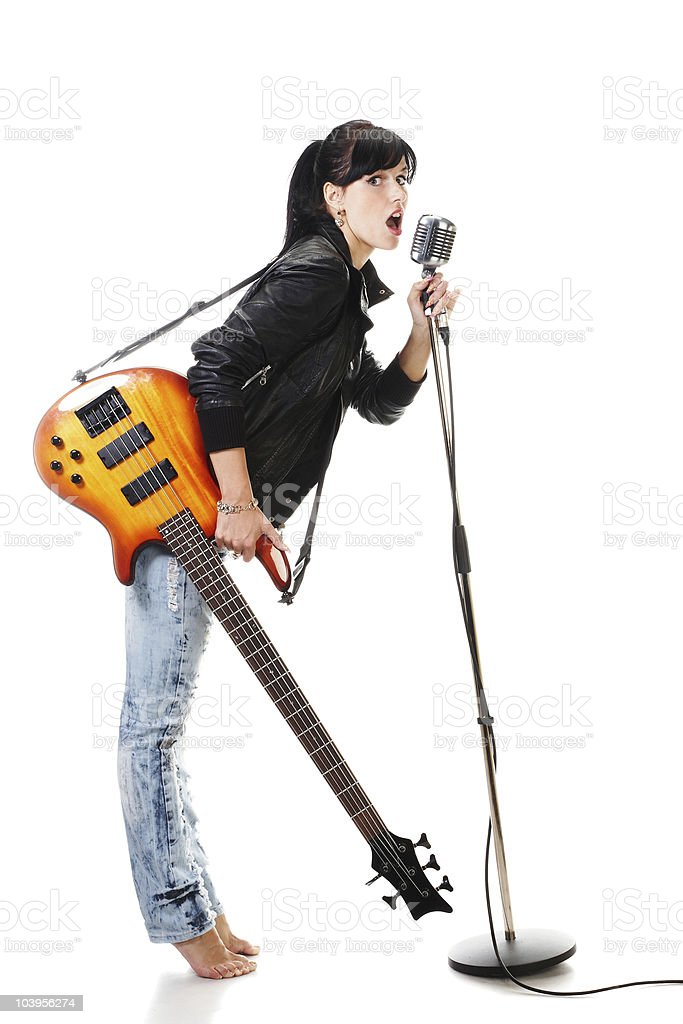 Rocker girl with electric bass signing to retro microphone royalty-free stock photo