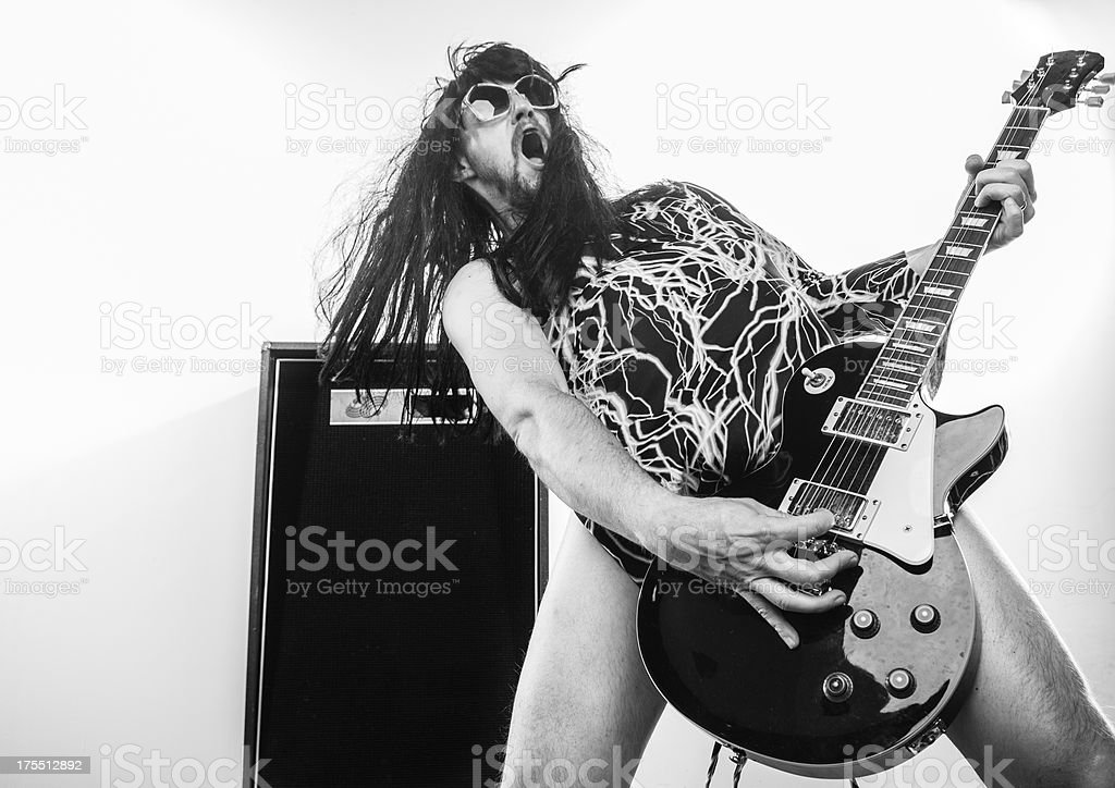 Rocker guy shredding his guitar with mouth open and sunglasses stock photo
