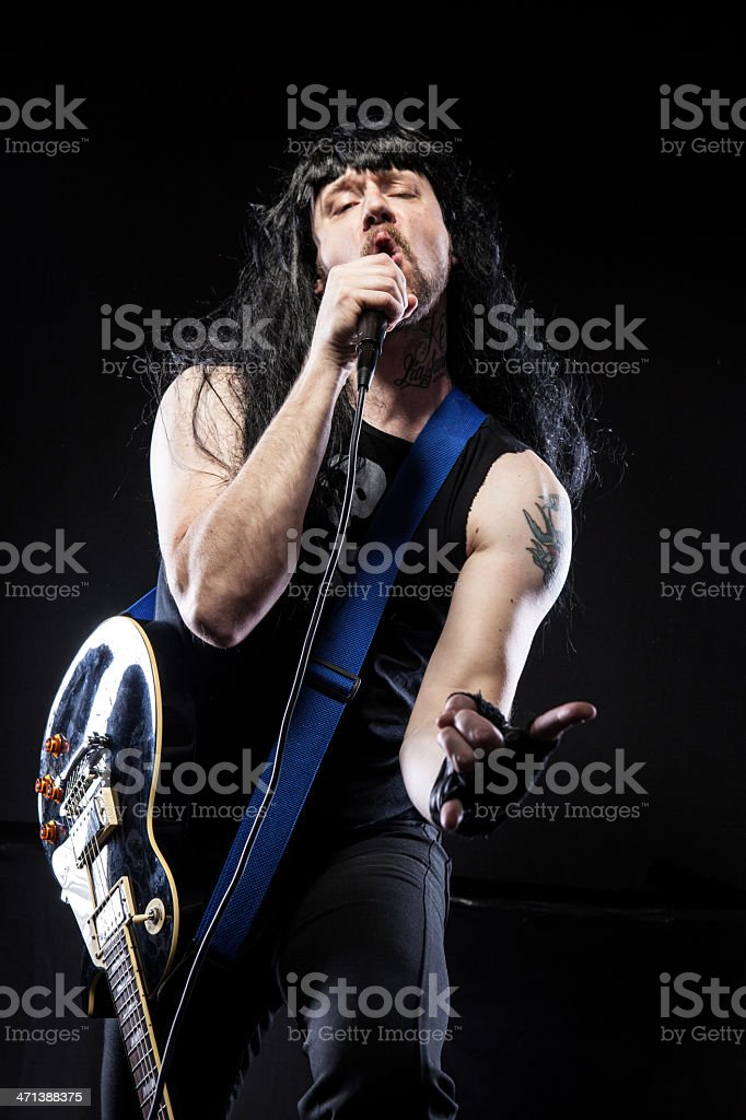Rocker holding mic posing with guitar making horned hand signal stock photo