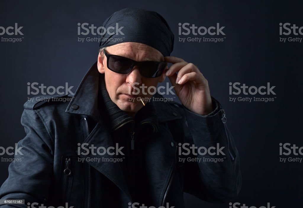 Rocker with sunglasses on black background. stock photo
