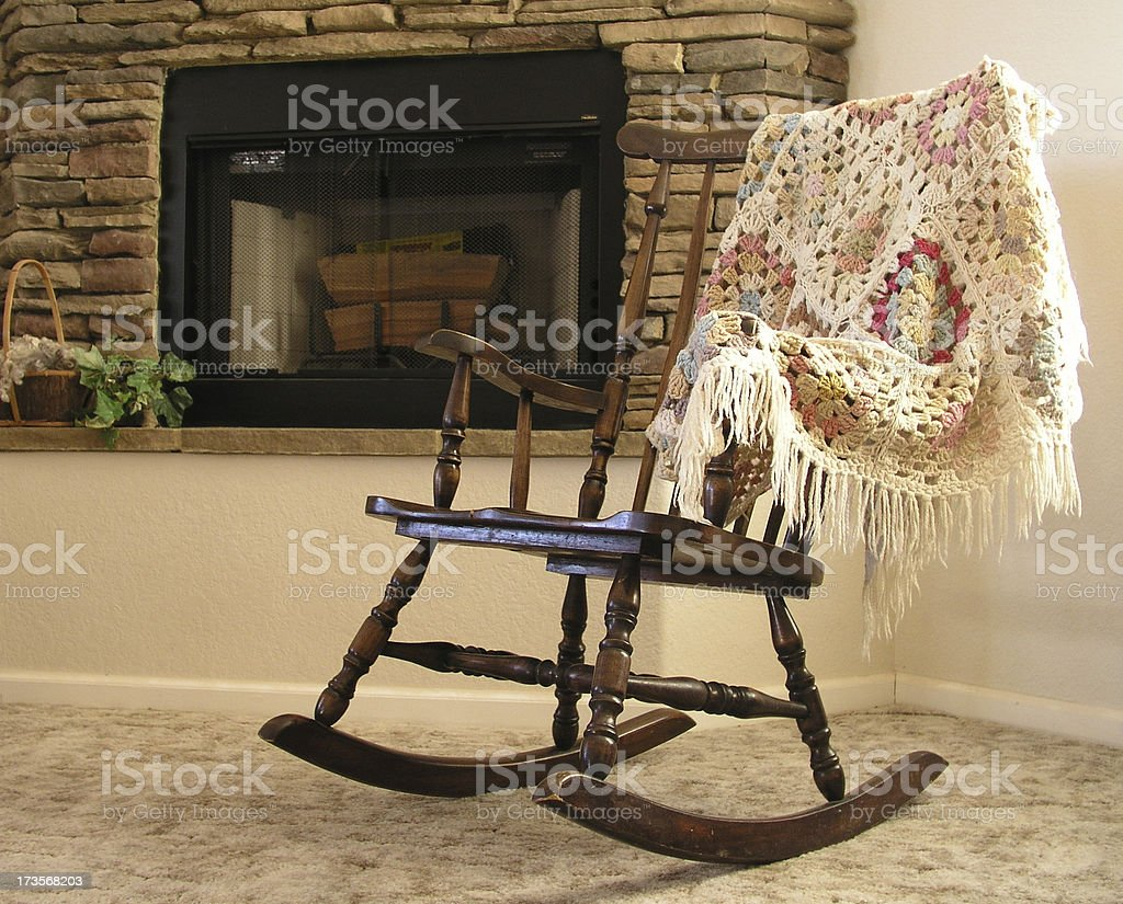 Rocking chair by fireplace stock photo