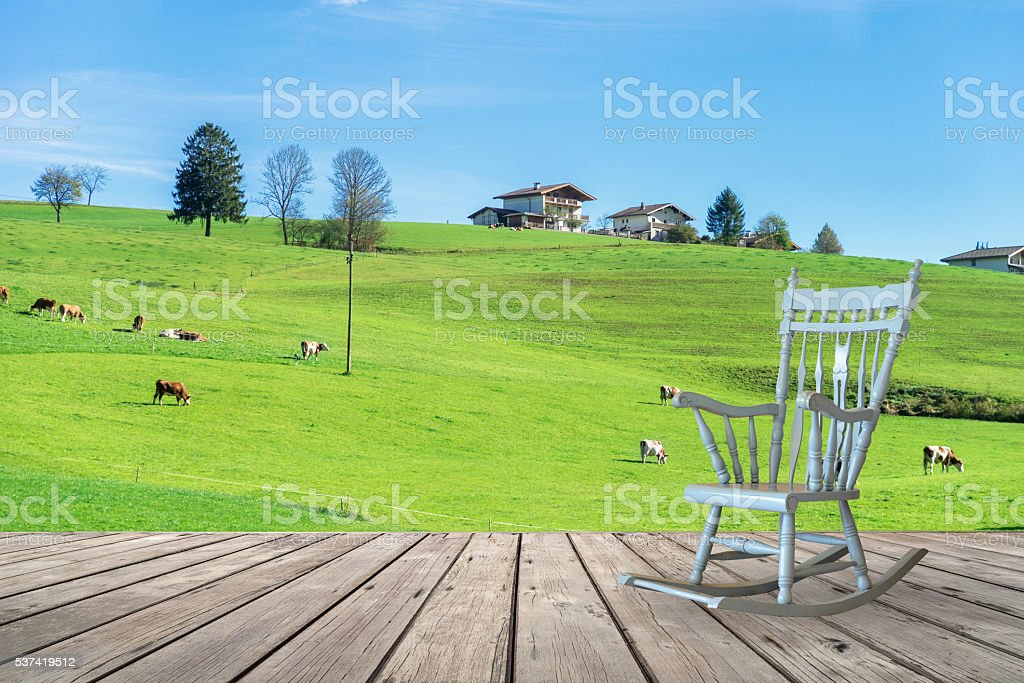 Rocking chair on wooden terrace with countryside view stock photo