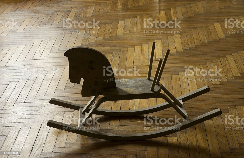 rocking horse on a parquet  [melancholy] royalty-free stock photo