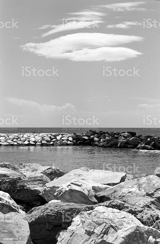 Rocks and clouds at the sea stock photo