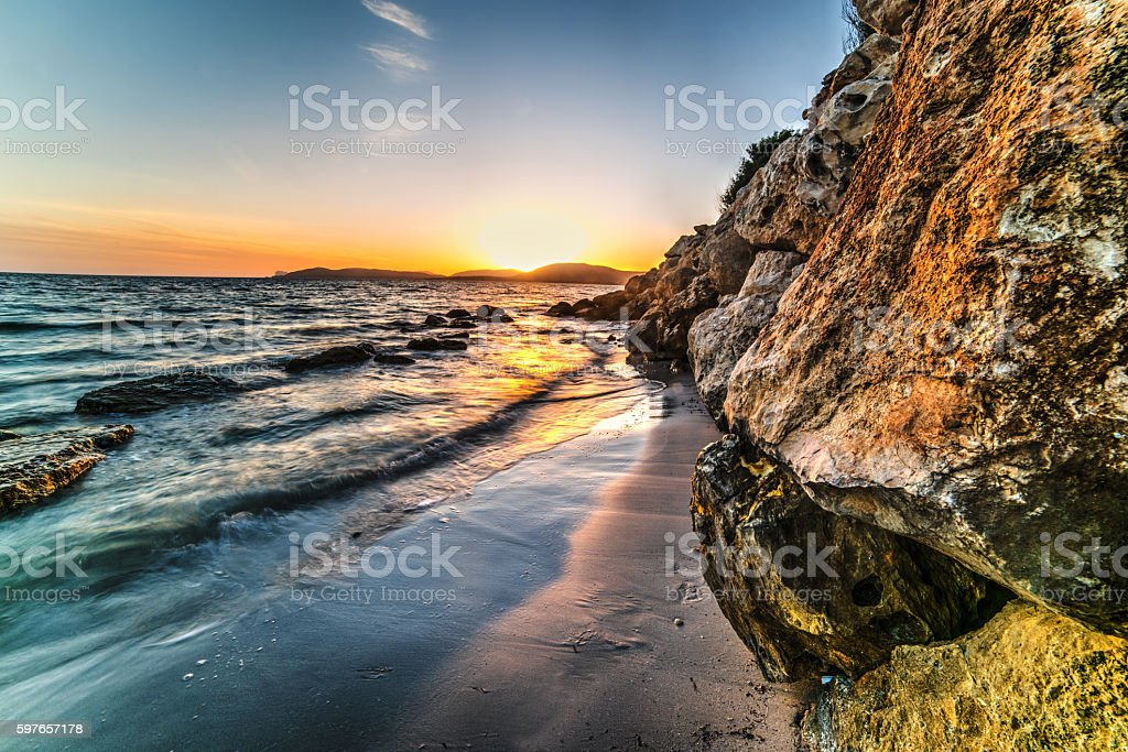 rocks and sand in Alghero shore at sunset stock photo
