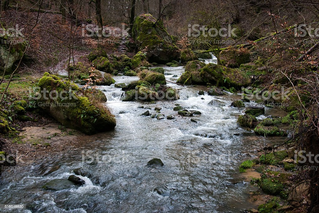 Rocks and water of Alsbaach creek in Mullerthal in Luxembourg stock photo