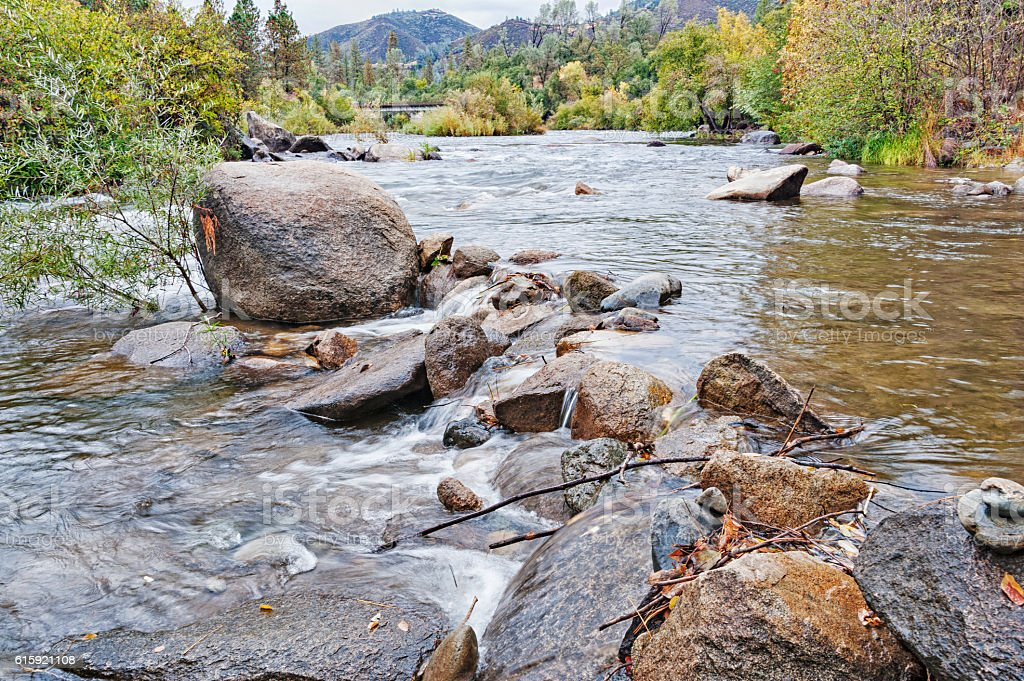 Rocks in American River with bridge and trees stock photo