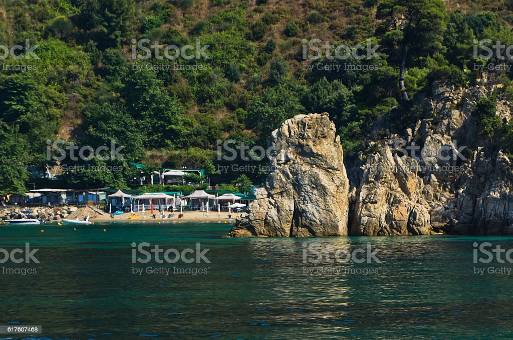 Rocks in front of a beach with emerald green water stock photo