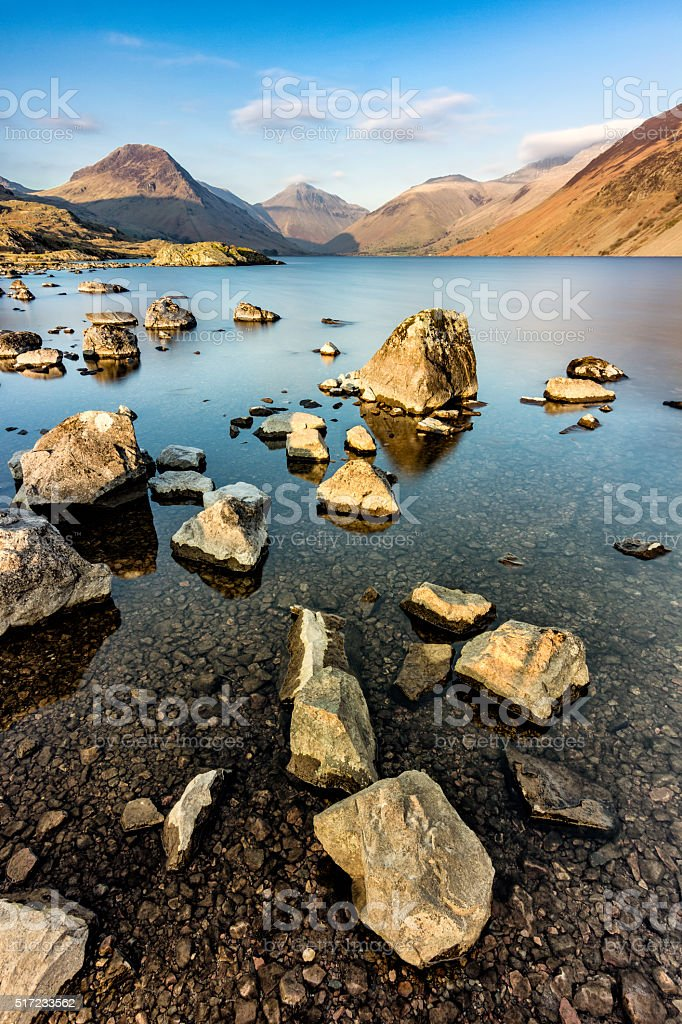 Rocks In Lake With Mountains And Clouds In Blue Sky. stock photo