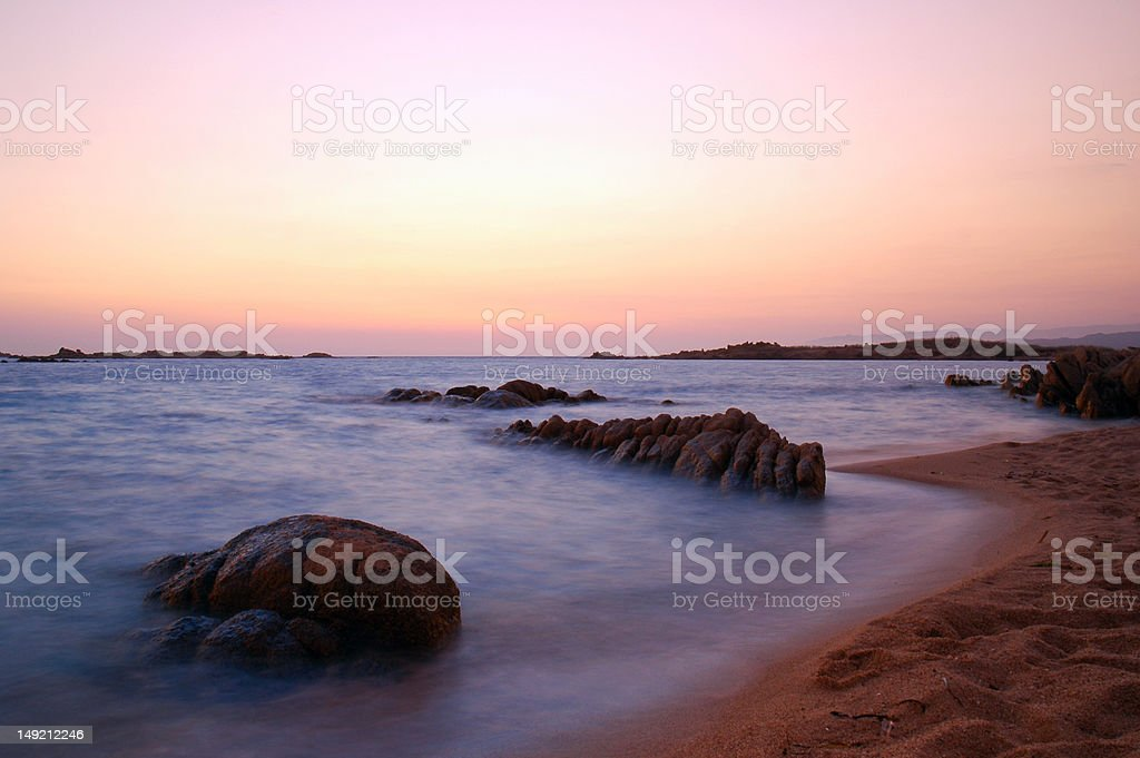 Rocks in the ocean at sunset stock photo