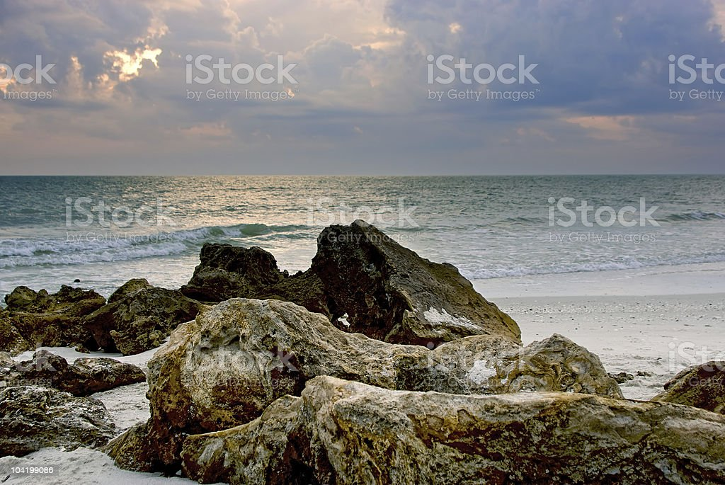 rocks on the beach at sunset stock photo