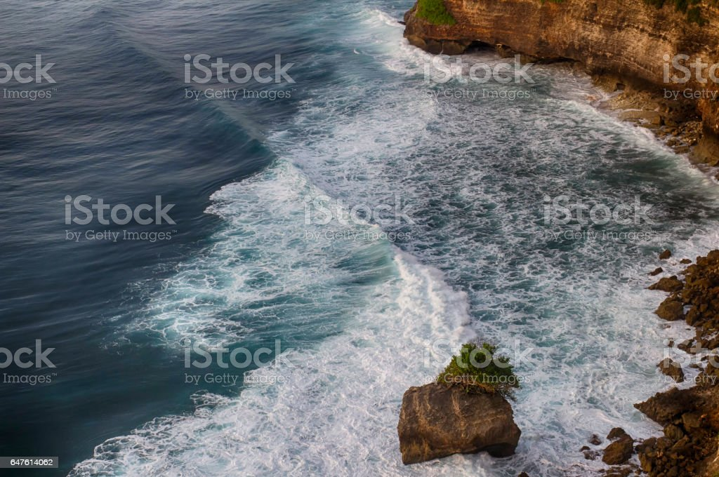Rocks on the shore of the raging ocean. Bali Island, Indonesia. stock photo
