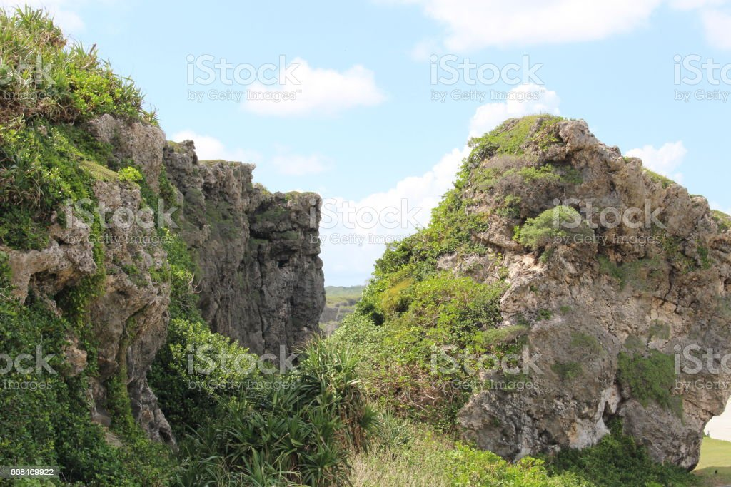 Rocks on the upper hill of a rocky mountain. A view from high places. Blue sky and sea, The beach and coastline beside the ocean in Miyako island, Okinawa, Japan stock photo