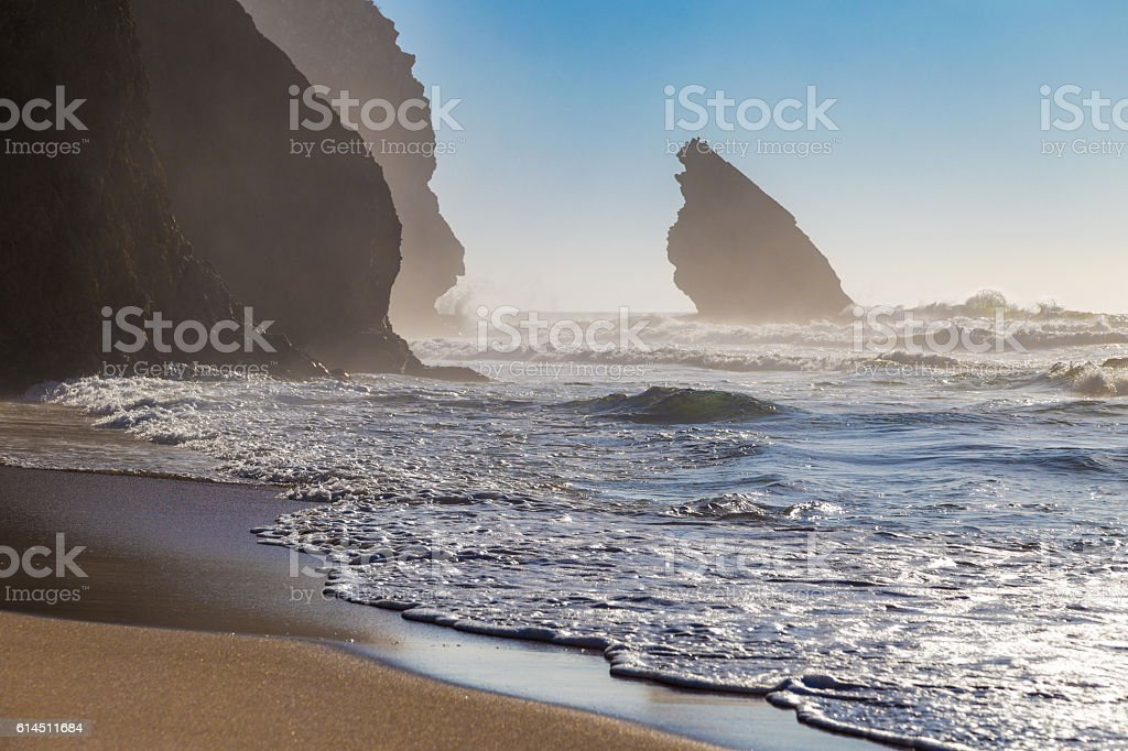 Rocks silhouettes, ocean waves, Adraga Beach (Praia da Adraga), Portugal stock photo
