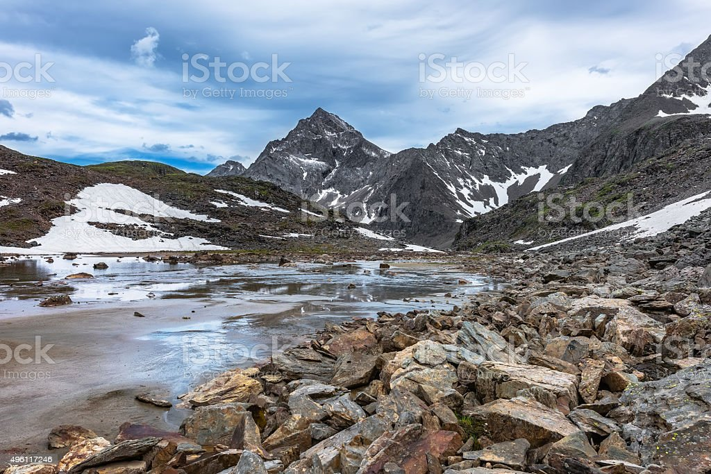 Rocks, water and alluvial sand in a small mountain valley stock photo