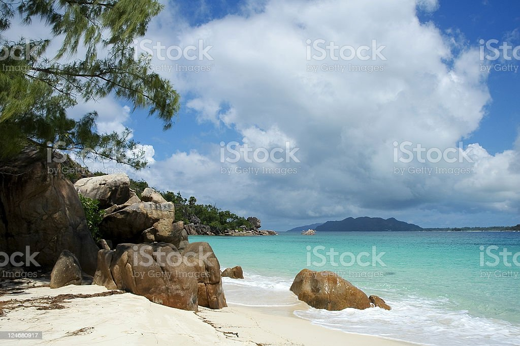 Rocky beach and azure water under white cloud stock photo