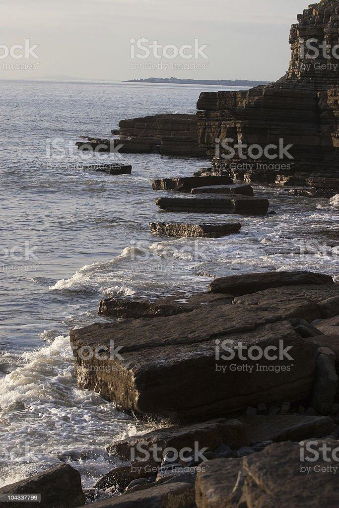 岩肌のビーチの夕暮れ ロイヤリティフリーストックフォト