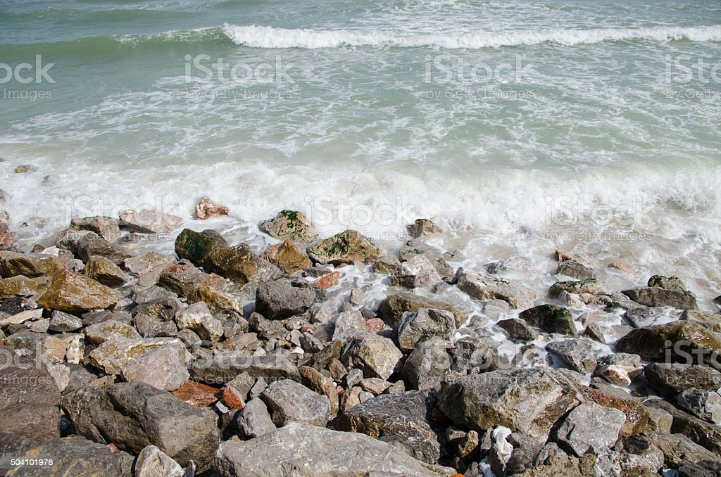 Rocky beach by the waves. stock photo