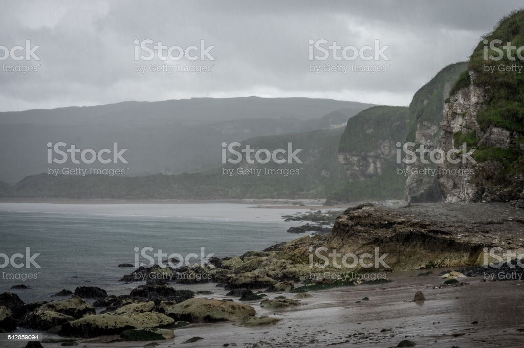 Rocky beach, cliffs and coastline in the rain stock photo