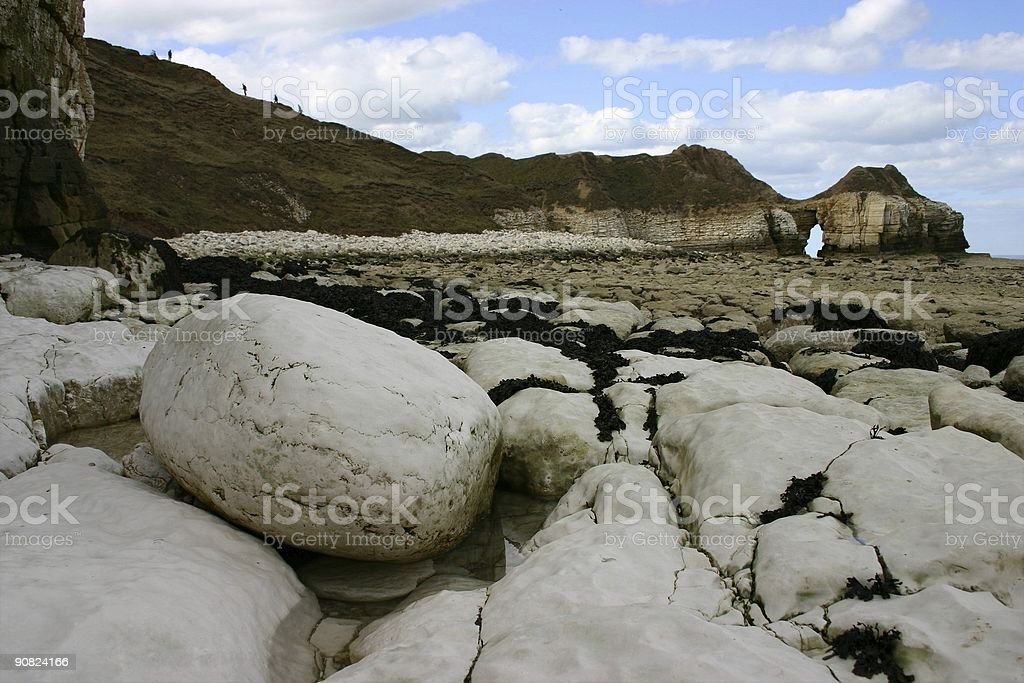 rocky beach leading to white cliffs stock photo