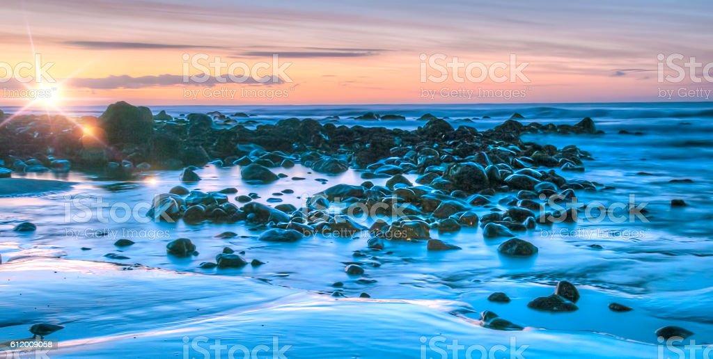 Rocky beach with flare stock photo