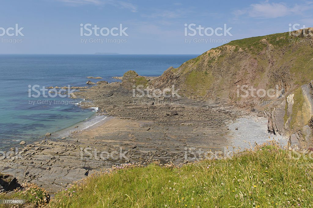 Rocky beach with lined rock strata and blue sea royalty-free stock photo