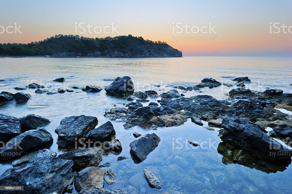 rocky bottom of the sea and sunrise over mountains royalty-free stock photo