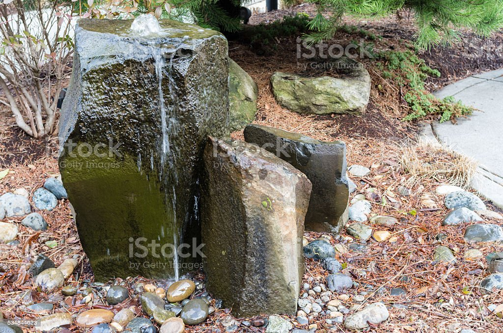Rocky bubbling water fountain in a courtyard garden stock photo