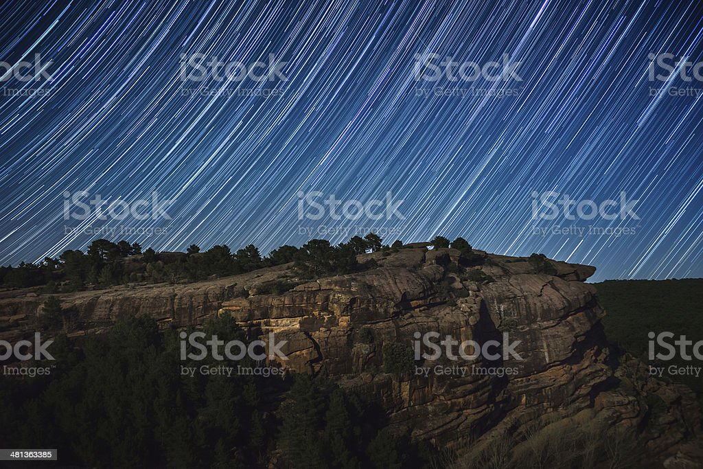 Rocky Cliff and star trails stock photo