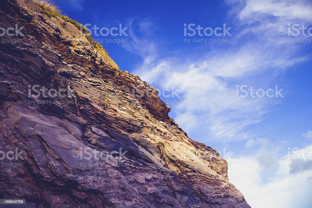 Rocky cliff side against blue sky royalty-free stock photo