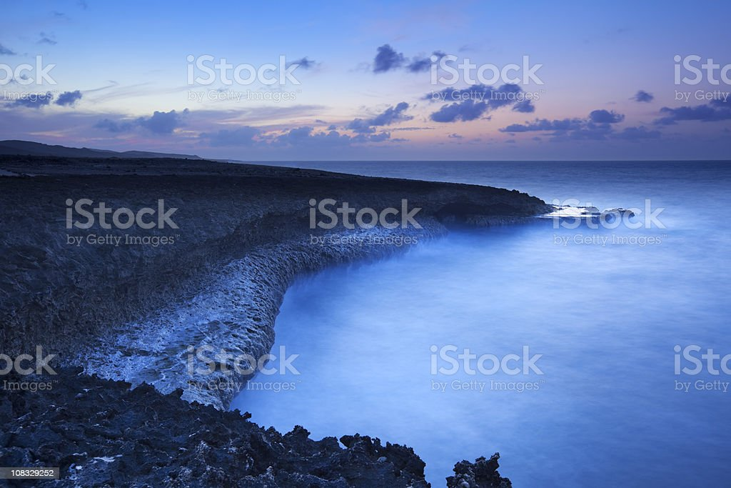 Rocky coast on the island of Curaçao at dusk royalty-free stock photo