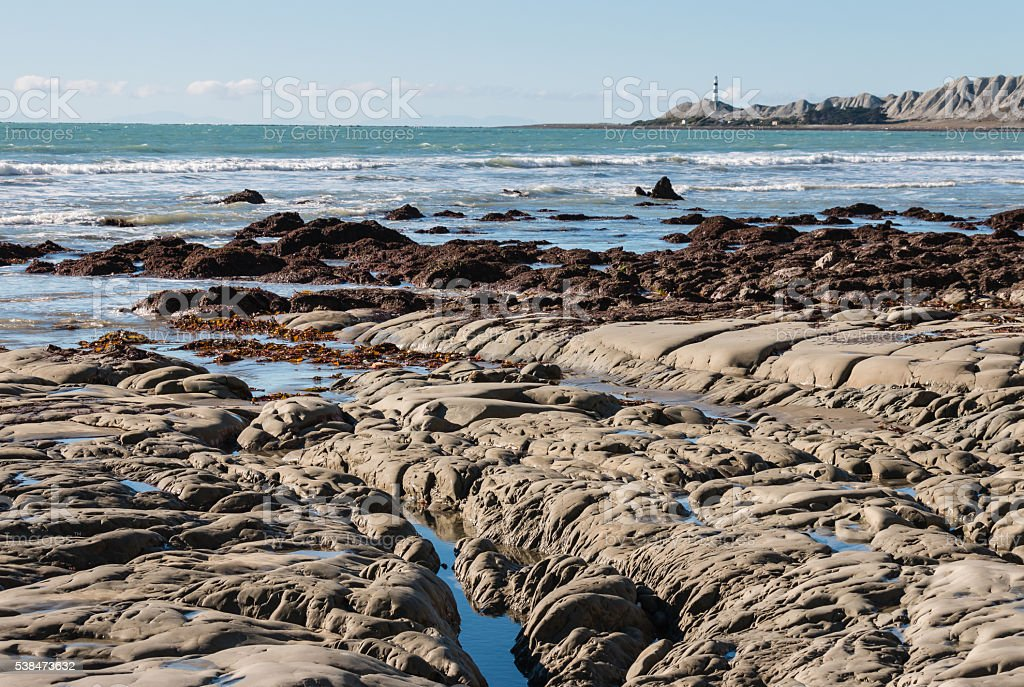 rocky coastline with lighthouse in distance stock photo