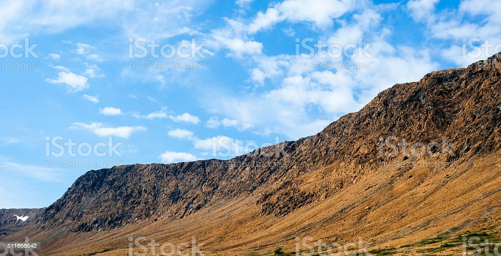 Rocky dry yellow cliff slope against light blue sky stock photo