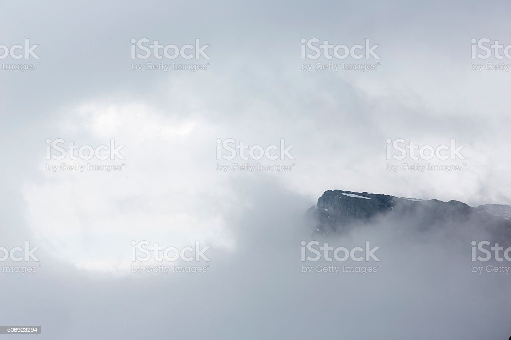 Rocky foggy mountain peak in the sky stock photo