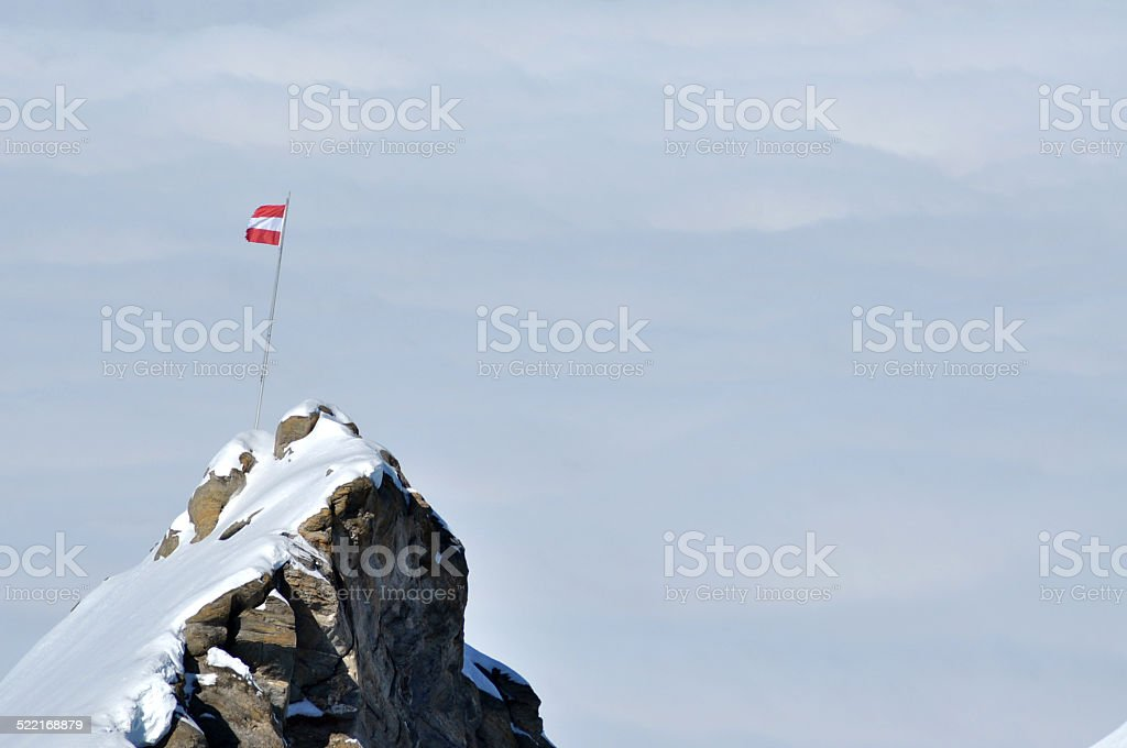 Rocky height in the Alps with the flag of Austria stock photo