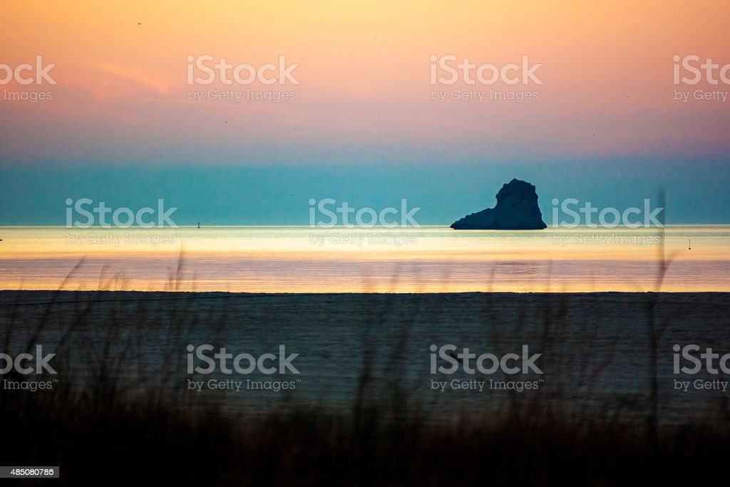 Rocky island at dawn. stock photo
