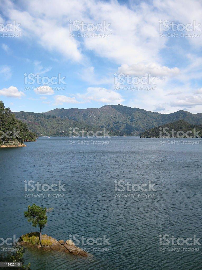 Rocky island, windswept water, cloudy sky stock photo