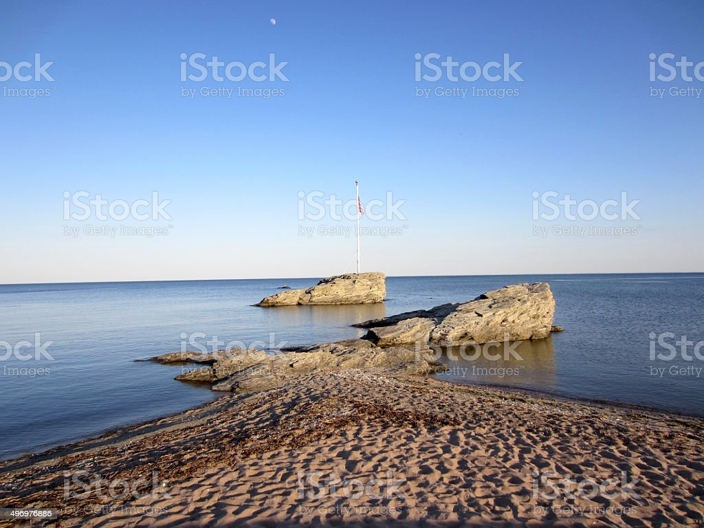 Rocky island with American flag. stock photo