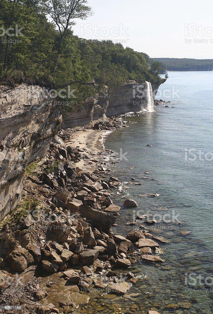 rocky lake shore with waterfall stock photo