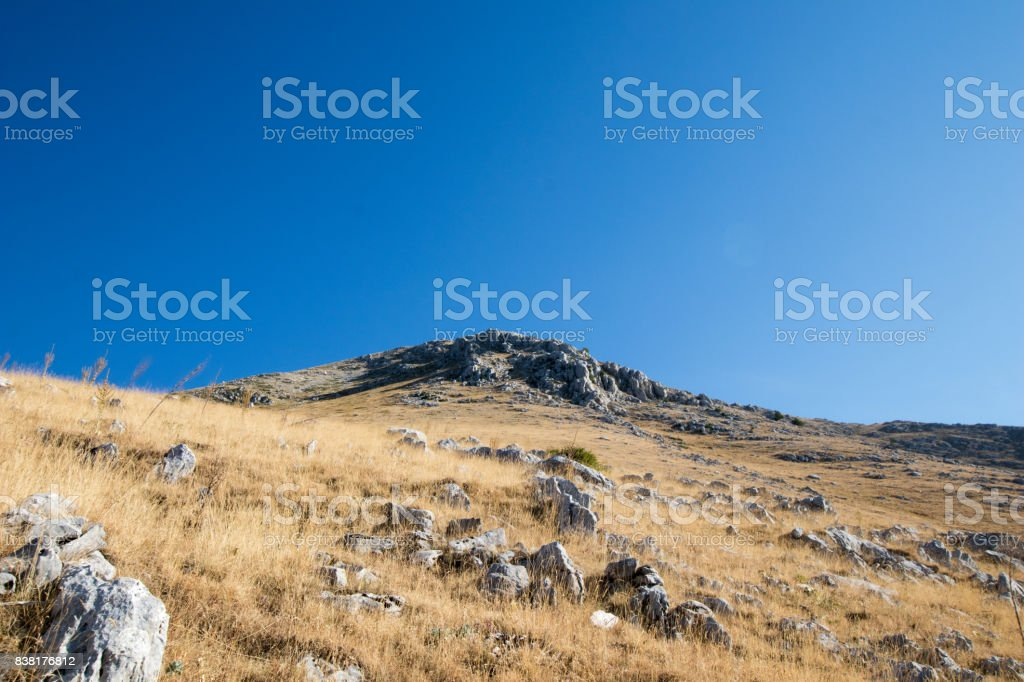 Rocky mountain with yellow grass fields and blue sky in the background. stock photo