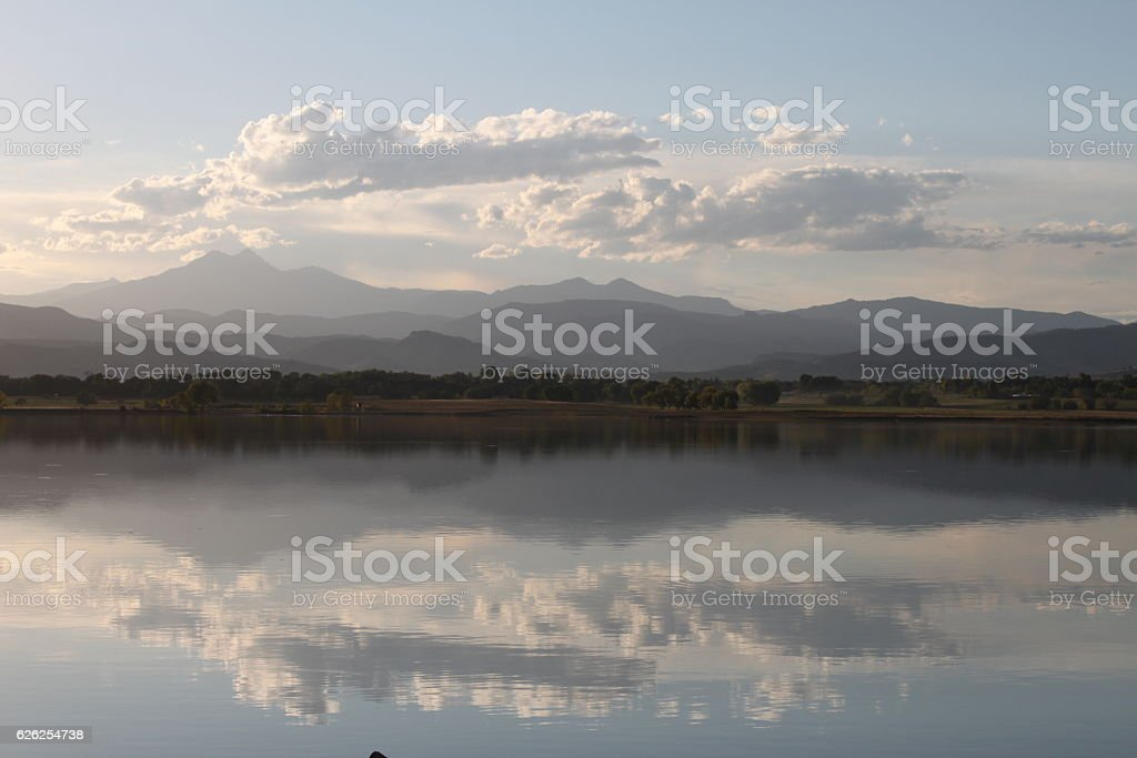 Rocky Mountains reflected in a lake with white clouds stock photo