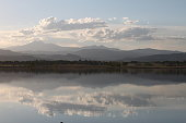 Rocky Mountains reflected in a lake with white clouds