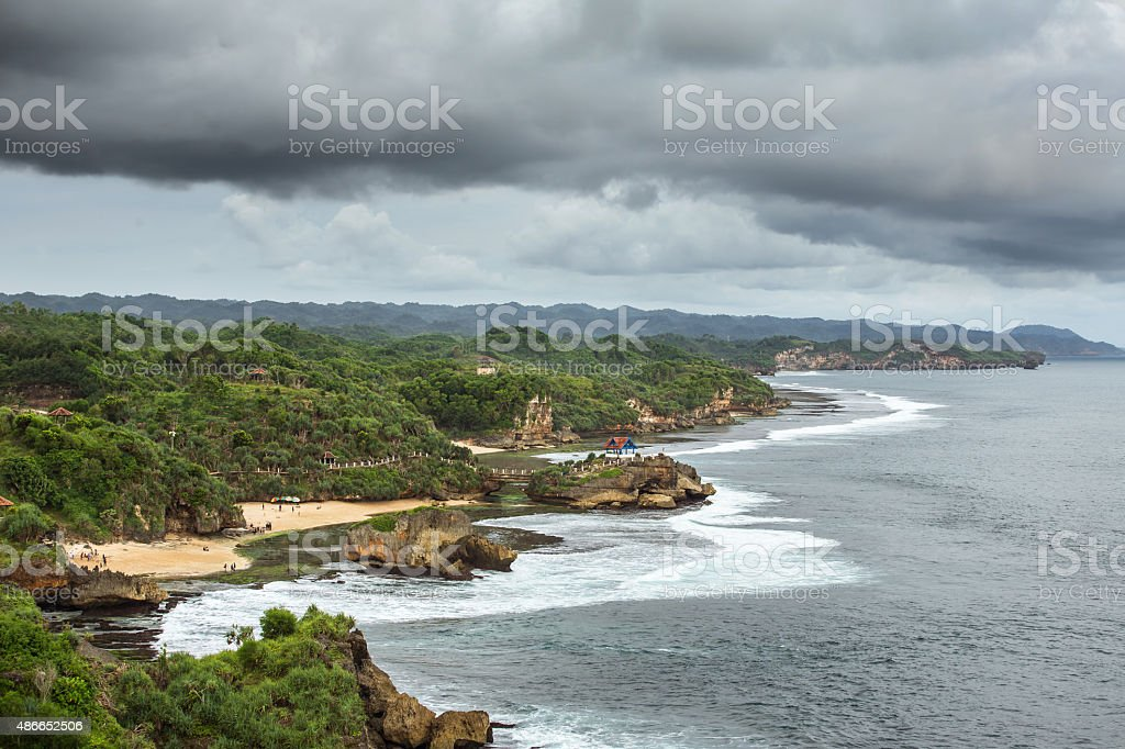 Rocky Pulau Jumpino island at Pantai Kukup beach in Java stock photo