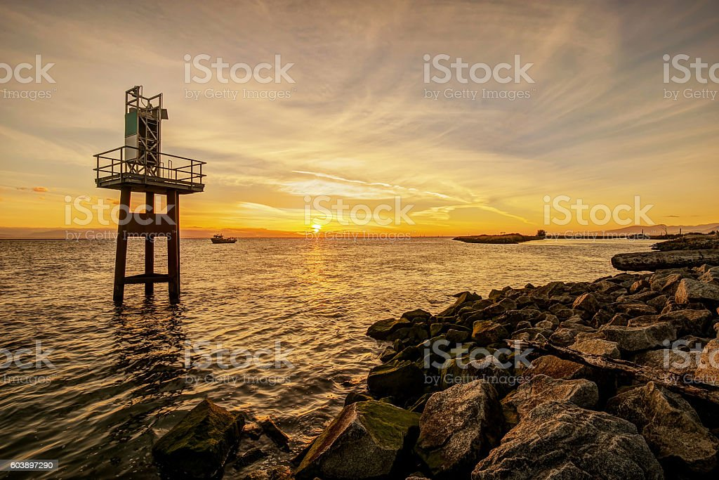 rocky sea beach at sunset stock photo
