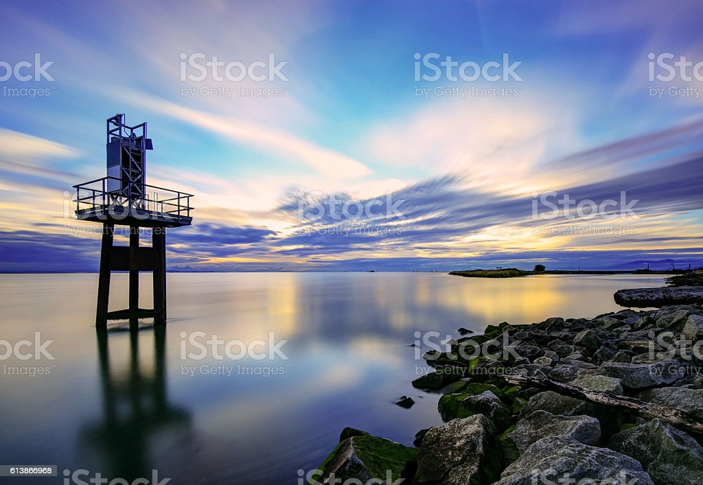 rocky sea beach at sunset, with dramatic sky stock photo