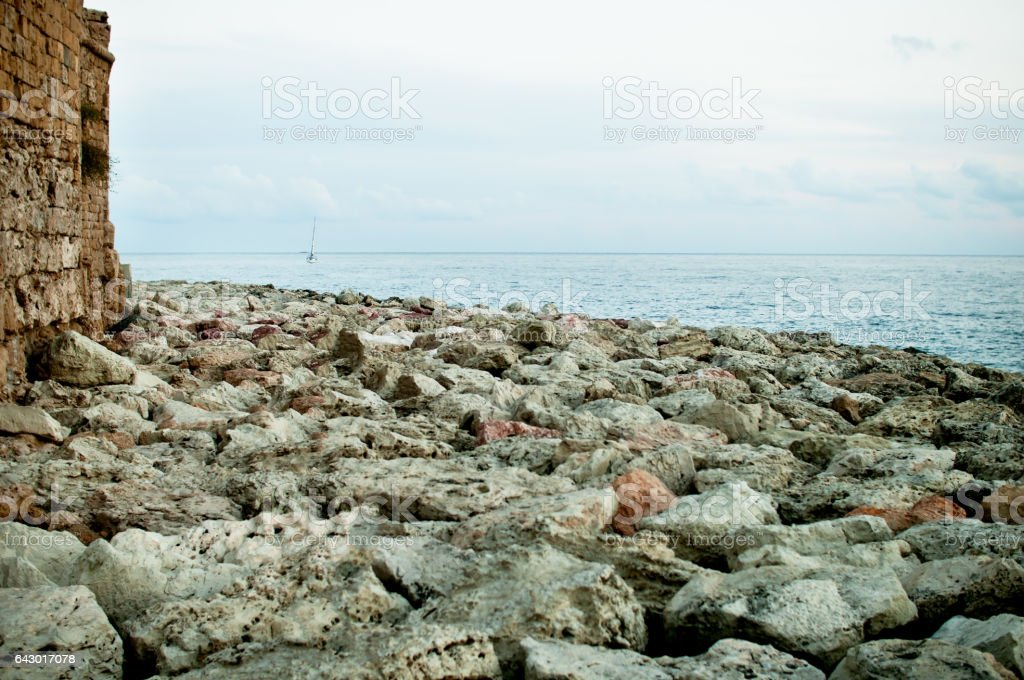 Rocky sea embankment with the elements of an ancient fortress stock photo