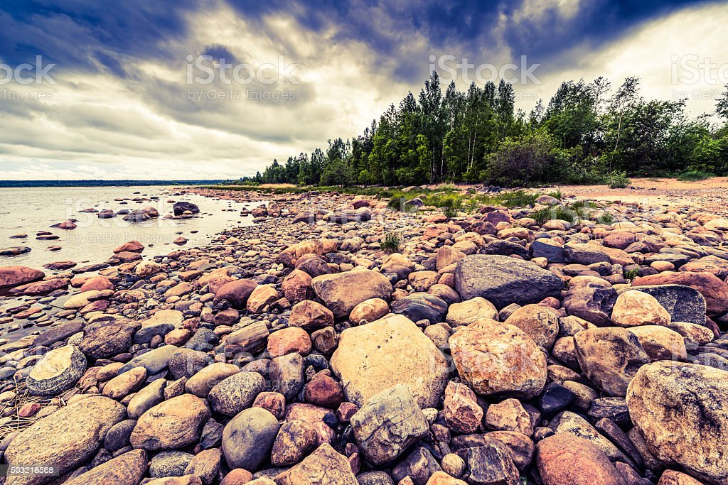 Rocky shore of the lake on a cloudy day stock photo