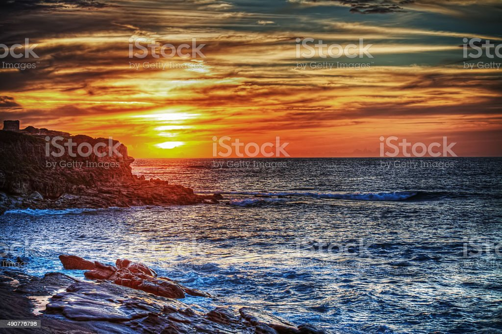 rocky shore under a colorful sky in Sardinia stock photo